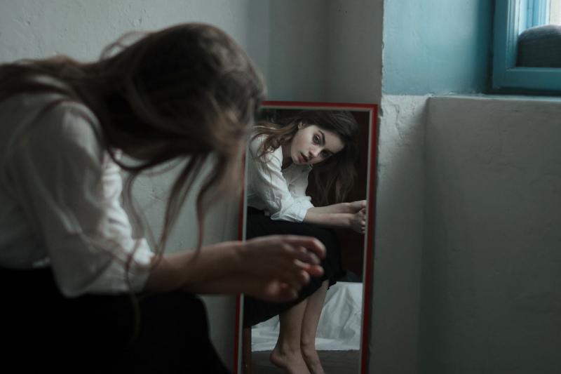sieviete skatās spogulī pieliekusies